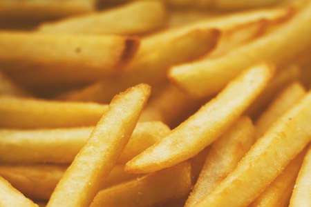 French fries close up. Saturated golden-yellow color. It can be used as background. The concept of fast food, delicious food, restaurants, cafes, etc.