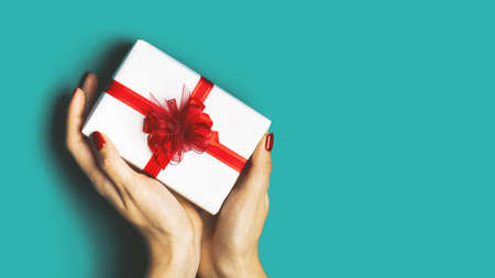 Beautiful female hands with a wrapped present on a trendy blue background. Perfect manicure. Copy space. Concept of the New Year, Christmas, Valentines Day, gifts