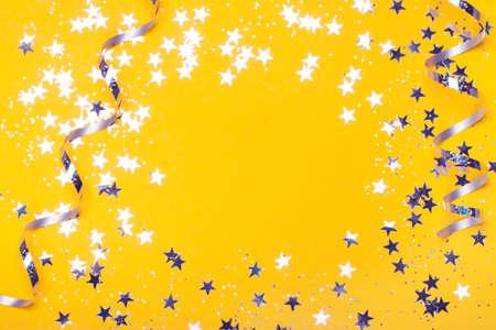 Glänzende Party-Streamer und Sterne auf dem heißen orangefarbenen Hintergrund. Flach liegen. Platz kopieren. Das Konzept der Feierlichkeiten, des Valentinstags, Weihnachten, Neujahr, Urlaub, Geburtstag usw.
