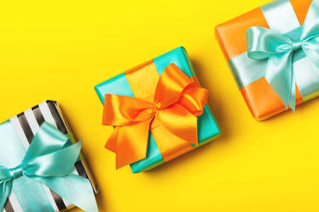 Line of attractive gifts on the yellow background. Present for St. Valentines day, weddings, engagements, Mothers Day, birthday, New Year, Christmas, holidays. Flat lay
