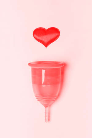 Transparent menstrual cup with heart on a pink background. The symbolic image of womens special days. Zero waste concept, eco-friendly lifestyle, reduced consumption