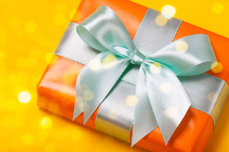 Attractive gift on a trendy orange background. Close up. Present for St. Valentines day, weddings, engagements, Mothers Day, birthday, New Year, Christmas, holidays. Flat lay