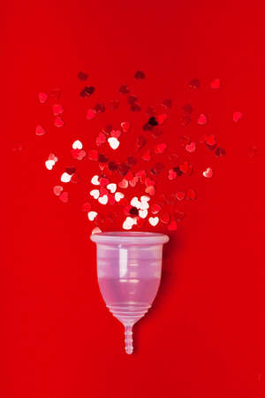 Transparent menstrual cup with red hearts on a red background. The symbolic image of womens special days. Zero waste concept, eco-friendly lifestyle, reduced consumption Stok Fotoğraf