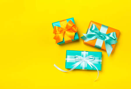 Set of attractive gifts on the yellow background. Trendy orange and green colors. Merry Christmas, St. Valentines Day, Happy Birthday and other holidays concept. Copy space. Flat lay