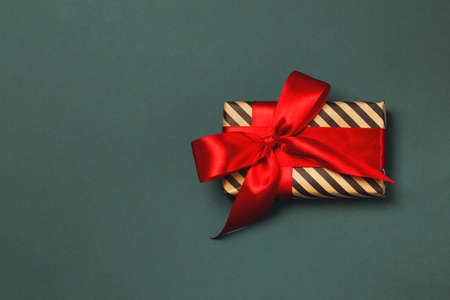 Luxuriously wrapped gift with red ribbon on the dark gray background. Trendy colors. Copy space. Merry Christmas, St. Valentines Day, Happy Birthday and other holidays concept.