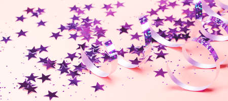 Shiny party streamers and stars on the pink background. Banner format. Close up. The concept of celebrations, the Day of St. Valentine, Christmas, New Year, holiday, birthday, etc.