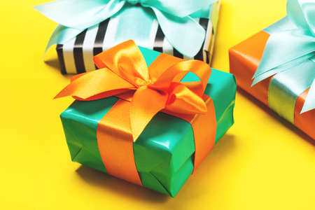 Set of attractive gifts on the yellow background. Trendy orange and green colors. Merry Christmas, St. Valentines Day, Happy Birthday and other holidays concept Stockfoto