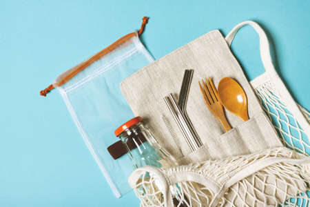 Set of reusable items for an eco-friendly lifestyle. Eco bag, glass bottle for water, metal tubes, wooden fork and spoon. Zero waste concept, plastic-free, organic, eco-friendly shopping
