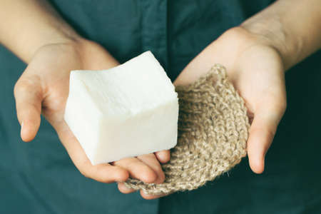 Eco-friendly cleaning kit. Organic soap and jute washcloth in the womans hand. Zero waste concept, plastic-free, eco-friendly shopping, vegan