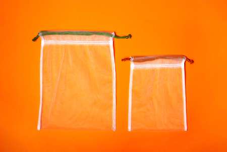 Set of reusable eco bags different sizes on a trendy orange background. An alternative to plastic bags. Copy space. Zero waste concept, plastic-free, eco-friendly shopping