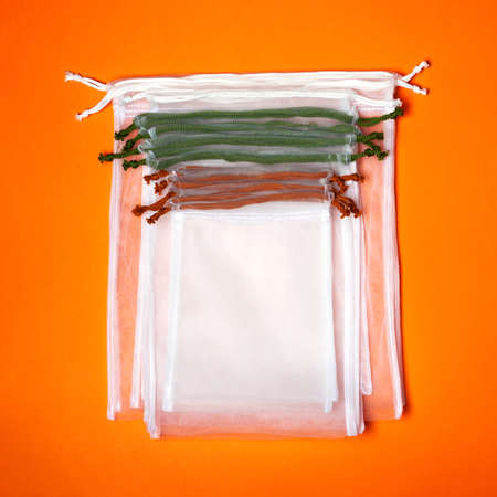 Set of reusable eco bags different sizes on a trendy orange background. An alternative to plastic bags. Zero waste concept, plastic-free, eco-friendly shopping