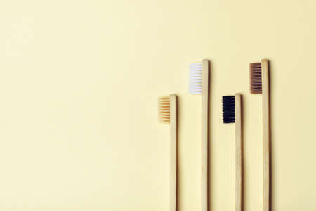 Four eco-friendly bamboo toothbrushes on a yellow background. Zero waste concept, plastic-free, organic, eco-friendly shopping Stock Photo