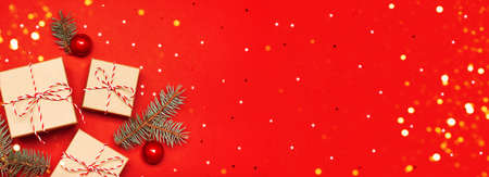 Web-banner with Christmas composition. Gifts, branches and holiday elements on the red background. Flat lay. Merry Christmas, New Year, winter concept. Stock Photo
