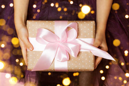 Luxurious gift in girls hands on the purple background. Perfect bow. Concept of the New Year, Christmas, Valentines Day, gifts