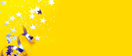 Banner with shiny party streamers and stars on the trendy yellow background. Copy space. The concept of celebrations, the Day of St. Valentine, Christmas, New Year, birthday, etc.