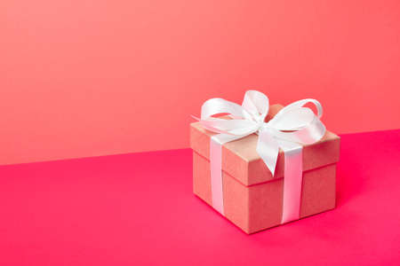 Trendy attractive minimalistic gift on the neon pink and coral background. Merry Christmas, St. Valentines Day, Happy Birthday and other holidays concept. Copy space.