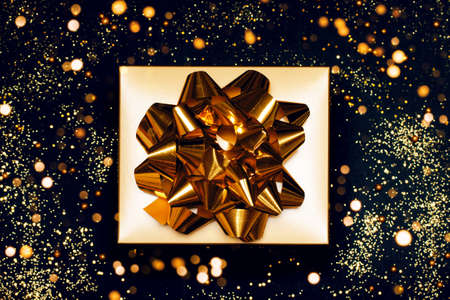 Trendy attractive minimalistic golden gift on the black festive background. Merry Christmas, St. Valentines Day, Happy Birthday and other holidays concept.