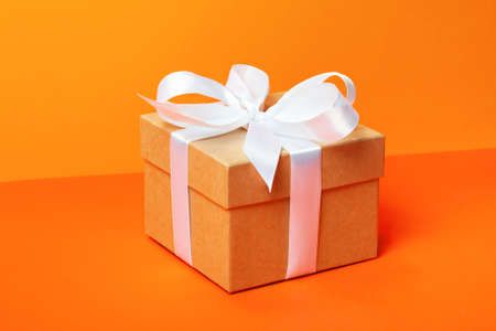 Trendy attractive minimalistic gift on the orange background. Merry Christmas, St. Valentines Day, Happy Birthday and other holidays concept.