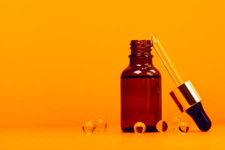 Face serum and vitamin capsules on the trendy orange background. Collagen, hyaluronic acid for skin care. Achievements of modern science in cosmetic to preserve beauty.