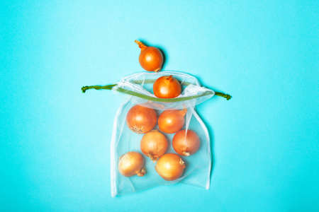 Organic golden onion in the eco bag on a trendy blue background. Zero waste concept, plastic-free, eco-friendly shopping, vegan
