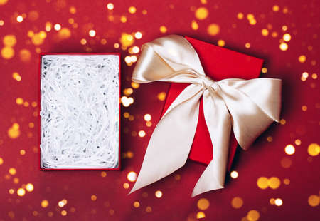 An opened gift box in which you can easily put any item. Red festive background and golden bow. Merry Christmas, St. Valentines Day, Happy Birthday and other holidays concept. Stock Photo