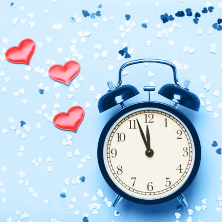 Alarm clock on a blue background with small hearts. The concept of the time of love, the time of date, the wedding, the day of St. Valentine, New Year