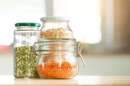 Glass jars with beans in the minimalistic interior. Peas and lentils as sources of vegetable protein. Zero waste concept, plastic-free, eco-friendly shopping, vegan Stock Photo