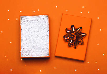 An opened gift box with a bow in which you can easily put any item. Orange festive background with stars. Merry Christmas, St. Valentines Day, Happy Birthday and other holidays concept. Stock Photo