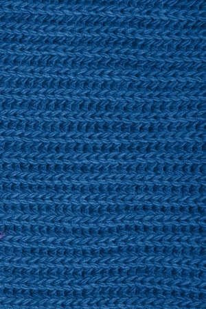 Knitted scarf texture. Classic blue color. The concept of cozy, comfort, warm, softness or winter