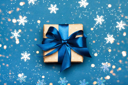 Attractive gift with blue ribbon on a blue background. Snow and lights. Merry Christmas, New Year, winter concept. Stock Photo