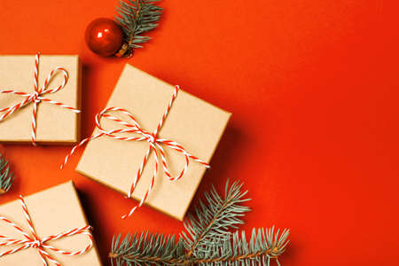Christmas composition with gifts, branches and holiday elements on the orange background. Flat lay. Merry Christmas, New Year, winter concept.