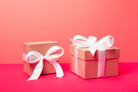 Trendy attractive minimalistic gifts on the neon pink and coral background. Merry Christmas, St. Valentines Day, Happy Birthday and other holidays concept.