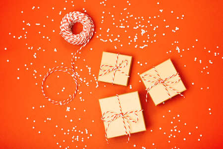 Minimalistic Christmas gift wrapping on the orange background. Flat lay. Merry Christmas, New Year, winter, zero waste concept.