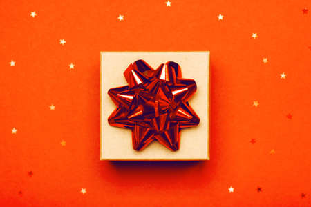 Attractive gift on a trendy orange background with stars. Present for St. Valentines day, weddings, engagements, Mothers Day, birthday, New Year, Christmas, holidays