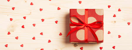 Web-banner with gift on a wooden background with hearts. Surprise your loved one. The concept of the day of St. Valentines, Mothers Day, birthday, New Year, Christmas, holidays.
