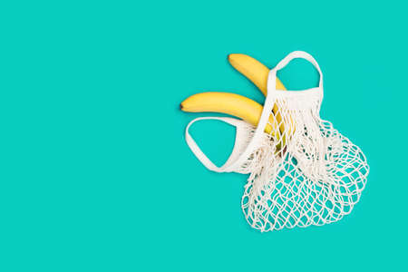 Two bright bananas in eco bag on a mint background. Zero waste concept, plastic-free, eco-friendly shopping, vegan