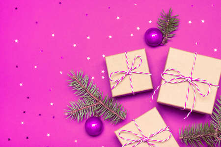 Christmas composition with gifts, branches and holiday elements on the violet background. Flat lay. Merry Christmas, New Year, winter concept.