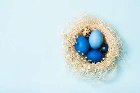 Easter eggs in blue colors in a nest. Copy space. The concept of stylish decoration for Easter, greeting cards, etc. Flat lay