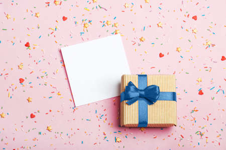 A gift in kraft box with blue bow and paper for notes on a pink background with decorations. Surprise your loved one. The concept of the day of St. Valentines, birthday and other holidays. Flat lay