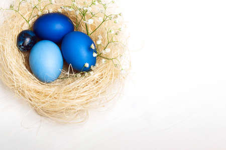 Easter eggs in blue colors in a nest. Copy space. The concept of stylish decoration for Easter, greeting cards, etc.