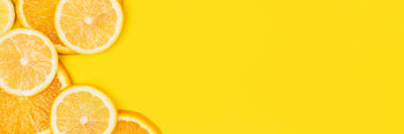 Juicy citrus on a yellow background. Bright vitamin photo. Copy space, web-banner format. Stock Photo