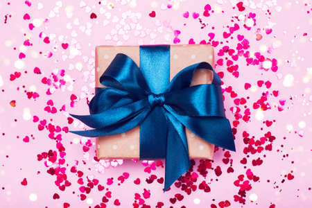 A gift in kraft box with blue bow on a pink background with hearts. Surprise your loved one. The concept of the day of St. Valentines, birthday and other holidays. Flat lay