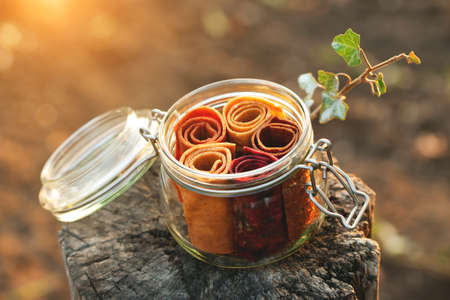 Glass jar with fruit pastille roll-up on a natural background. The concept of healthy organic sweets, proper nutrition, zero waste, vegan.