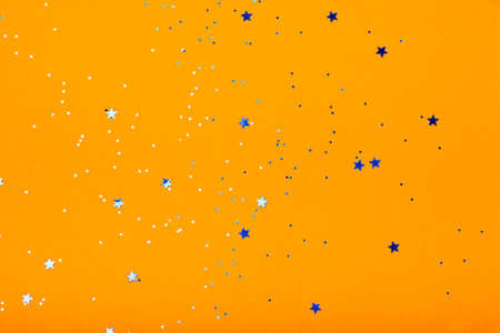 Orange festive background with blue stars and sparkles. The concept of the celebration, the day of St. Valentine, New Year, birthdays, ceremonies, events, etc.
