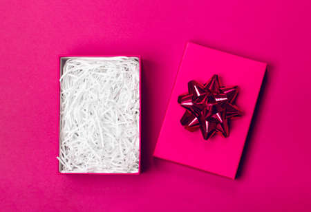An opened gift box with a bow in which you can easily put any item. Pink trendy background. Merry Christmas, St. Valentines Day, Happy Birthday and other holidays concept.