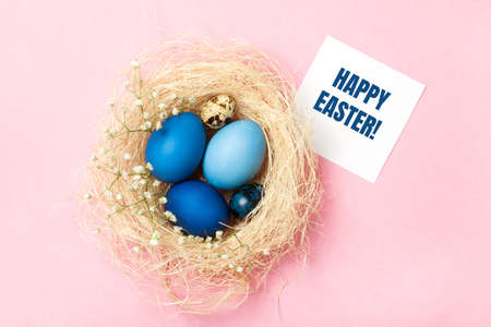 Easter eggs in blue colors in a nest on the pink background. Greeting card. Stylish decoration for Easter, zero waste concept. Flat lay.