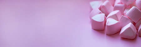 Heap of marshmallows in the shape of hearts on a pink background. Banner format. The concept of St. Valentines Day, love, sweets