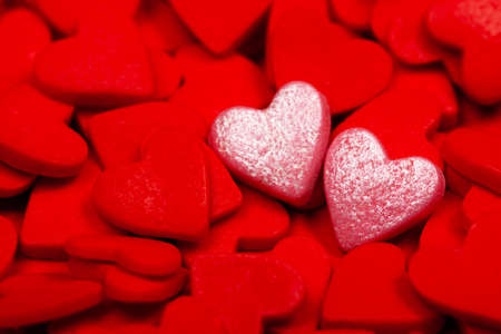 Two sweet loving hearts among many red hearts. The concept of St. Valentines Day, love, couple, sweets