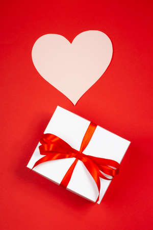A gift with paper for notes in the shape of a heart on a red background. Surprise your loved one. The concept of the St. Valentines day, birthday and other holidays. Flat lay Stock Photo