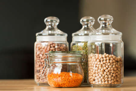 Glass jars with beans in the minimalistic interior. Peas, lentils, mung bean, beans and chickpeas as sources of vegetable protein. Zero waste concept, plastic-free, eco-friendly shopping, vegan Stock Photo